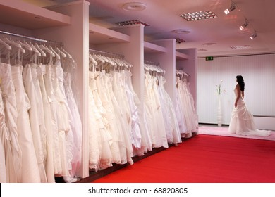 Pretty girl in a wedding gown in the bridal shop.