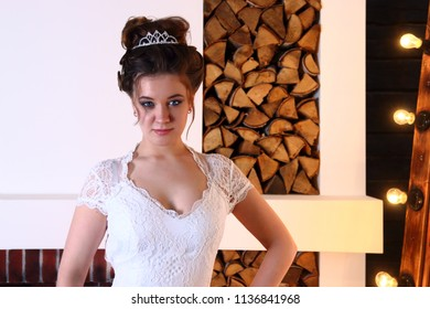 Pretty girl in white dress poses in studio with logs and lamps
