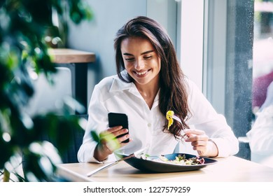 Pretty girl in white shirt sitting in cafe, eating and holding mobile phone, freelance work in progress, work from home concept, smiling.