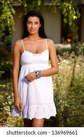 Pretty girl in white summer dress standing in the garden, smiling.