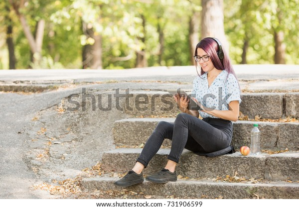 Pretty girl working on tablet on a natural background. Progressive studying concept. Copy space.