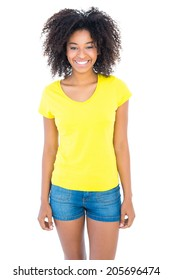Pretty girl in yellow tshirt and denim hot pants smiling at camera on white background