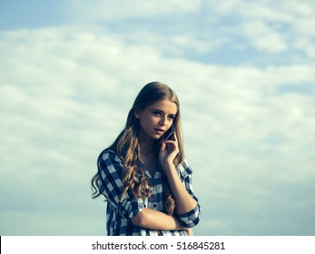 Pretty girl young beautiful woman with long curly blond hair in shirt talks on phone outdoors on blue cloudy sky