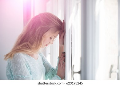 Pretty girl or young woman with blond, long hair and cute face leaned against window frame on sunny day. Future perspective and outlook