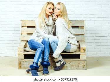 Pretty girls or beautiful cute women, sexy fashion model with blond hair in jeans and sweatshirt sits on wooden pallet sofa on white brick wall