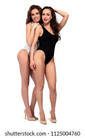 Pretty girls in black and white swimsuits are posing against a white background, isolated