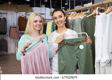 Pretty girls choosing new garment in fashion store