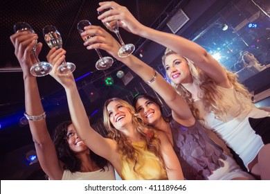Pretty girls holding champagne glass in a nightclub