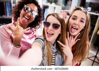Pretty girls wearing sunglasses fooling around taking selfie showing tongue and horn gestures in clothing shop