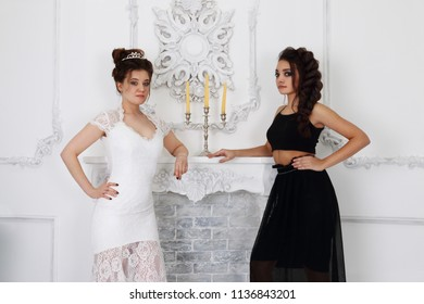 Pretty girls in white and black pose near fireplace with candles in studio