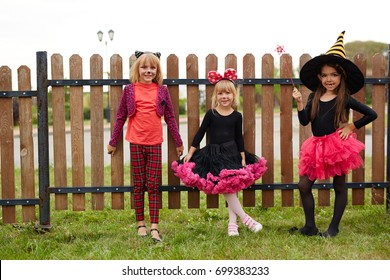 Pretty girls in witch costumes celebrating halloween outdoors