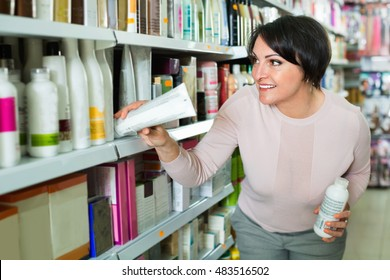 Pretty glad charming woman choosing hair care products in shop and smiling