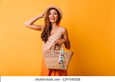 Pretty glamorous girl touching her straw hat. Studio portrait of joyful young woman with summer bag.