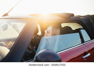 Pretty and good looking young blonde woman or model, sits inside convertible cabriolet car, before opening roof, smiles during beautiful sunset. proud new car owner teenager dream come true