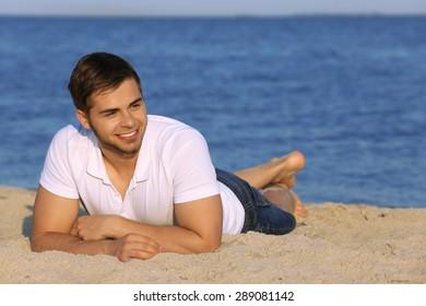 Pretty guy lying on beach
