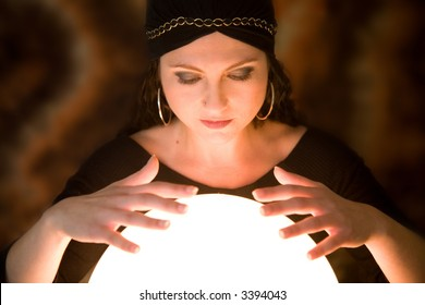 Pretty gypsy woman with her hands above her crystal ball predicting the future