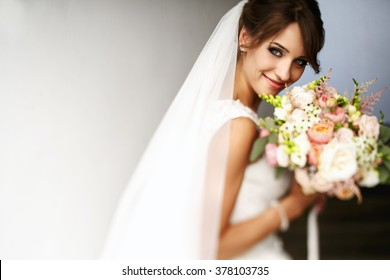 Pretty happy bride in luxury dress with bouquet of roses