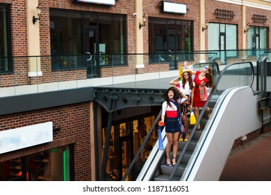 Pretty happy bright women female girls friends tourists in colorful dresses, hats and high heels in escalator with shopping bags shopping in shopping mall in summer. Shop sales, black Friday.