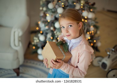 A pretty happy brown-haired girl is holding gifts at the Christmas tree. New year and Christmas.