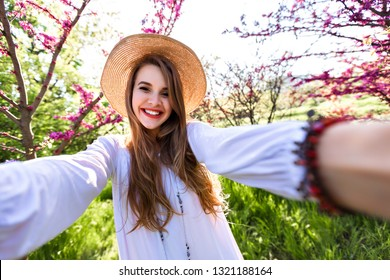 Pretty happy easy going woman making selfie smiling and laughing, wearing straw hat and elegant white top