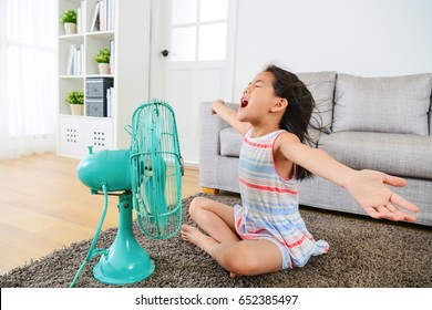 pretty happy female kid opening arms enjoying cool wind from electric fan and sitting on floor in living room at summer vacation.