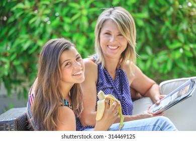 pretty happy girl enjoying a banana with her smiling blond mother reading a book