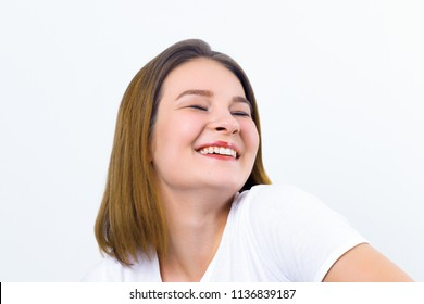 Pretty happy girl teenager in t-shirt laughs in white studio