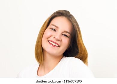 Pretty happy girl teenager in t-shirt smiles in white studio