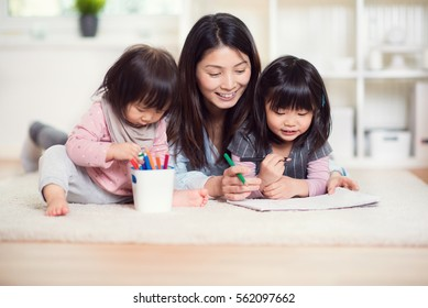 Pretty happy japanese mother play with her two cute little daughters at home