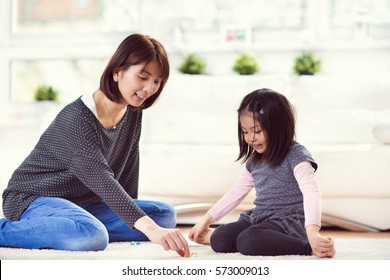 Pretty happy japanese mother play with her cute little daughter on carpet at home