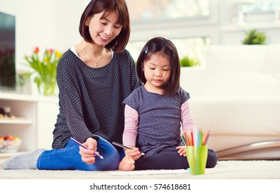 Pretty happy japanese mother play and draw with her cute little daughter at home