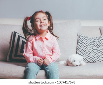 Pretty happy little girl in casual wearing sitting on sofa with toy dog and smiling