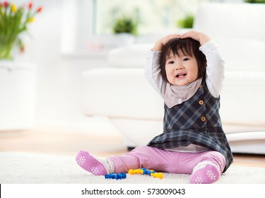 Pretty happy little japanese child girl playing on white capet at home