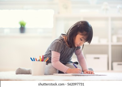 Pretty happy little japanese girl lying and drawing with pencils on white capet at home