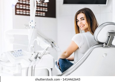 Pretty happy and smiling dental patient sitting in the dental chair at the dental office