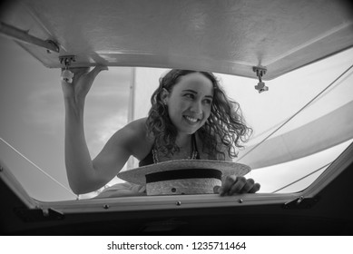 A pretty, happy, smiling girl peering into a door hatch on a sail boat.