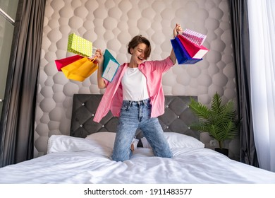 pretty happy woman having fun jumping on bed at home with colorful shopping bags on black friday sale discount excited
