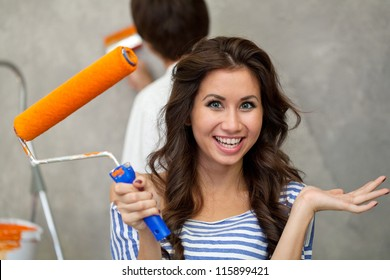 Pretty happy woman looking at camera while her husband painting wall