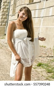 Pretty happy young brunette posing outdoors .