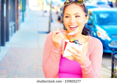 Pretty happy young pretty mixed race female eating frozen yogurt while looking away. Horizontal Shot.