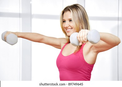 Pretty happy young woman exercising with free weights