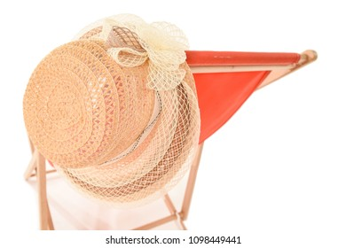 Pretty hat hanging on the back of a bright orange deckchair. Taken at an angle so that focus is on the hat with the deckchair slightly out of focus into the background. Space for text.