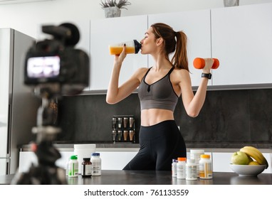 Pretty healthy young girl recording her video blog episode about healthy food additives while standing at the kitchen at home and holding dumbbell
