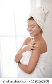 Pretty healthy young woman wrapped in white towels standing in a bathroom with eyes closed and a happy smile in a spa treatment, wellness and personal hygiene concept