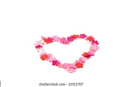A pretty heart made out of red and pink flowers on a white background.