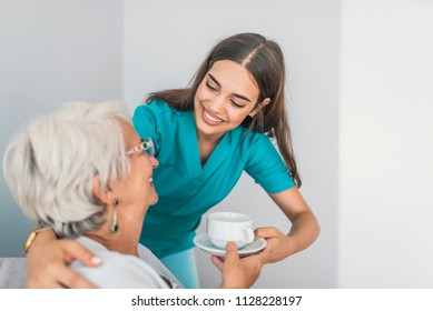 Pretty helpful carer talking with female patient. Health visitor and a senior woman during home visit. Supportive senior care assistant and smiling older woman in nursing home