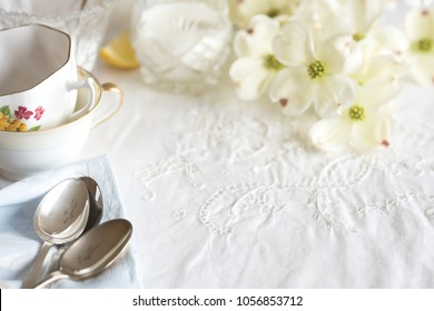 Pretty High Tea Party Table Setting with Cups, Spoons, and Flowers on a Vintage White Cloth with room or space in center for copy, text, or your words.  Horizontal with short focus and blur background