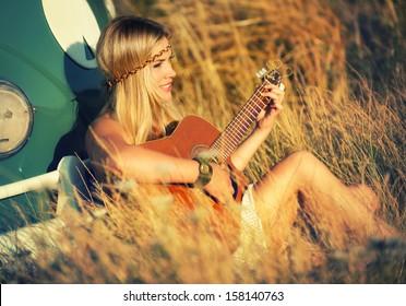 pretty hippie girl playing guitar