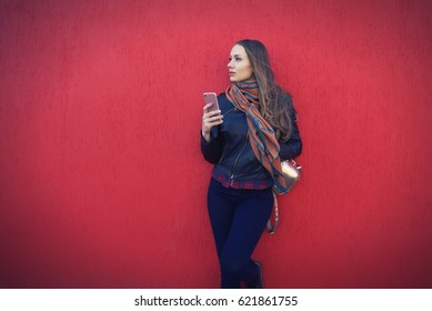 Pretty hipster girl sending text message to friends and spending all free time on social network outdoors using smartphone with 4G internet while standing near promotion background for your advertise