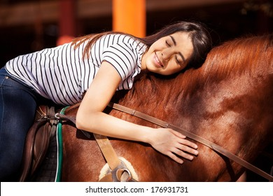 Pretty Hispanic brunette giving her horse a hug while riding him outdoors